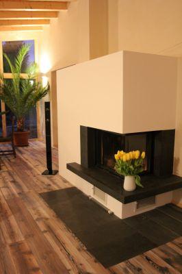 Abbildung: Wohnzimmer mit massivem Kamin und hochwertigem Parkett