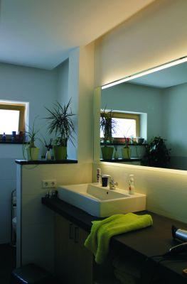 Abbildung: Ein Badezimmer mit Waschtischkonsole aus Naturstein und beleuchtetem Spiegel