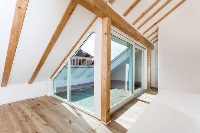 Abbildung: sichtbare Balken und viel Licht im Dachgeschoss