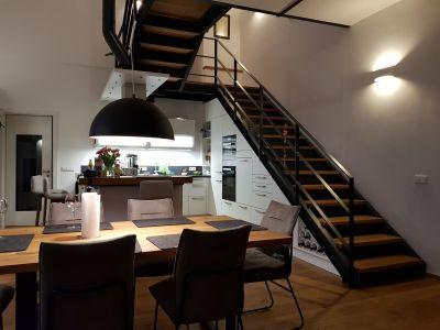 Abbildung: eine Stahltreppe mit Holzstufen, die Küche passt perfekt darunter
